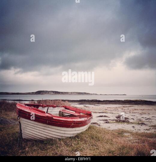 UK, Scotland, Inner Hebrides, Jura, Red and white boat on grass - Stock Image