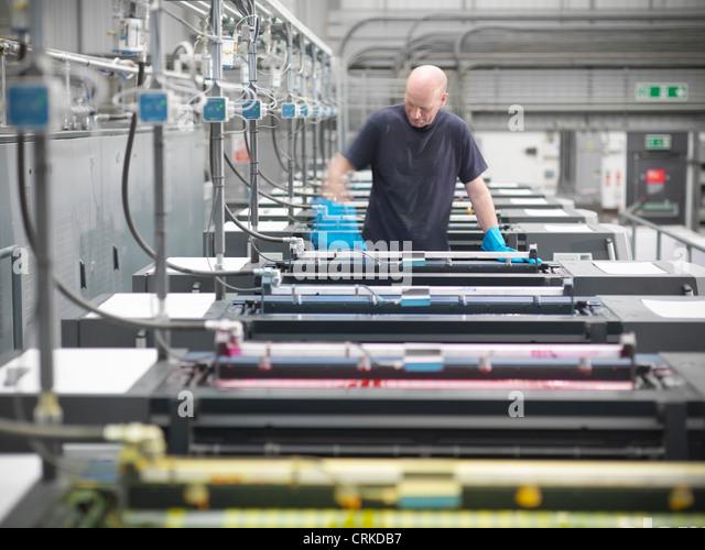 Printer inking printing press in shop - Stock Image