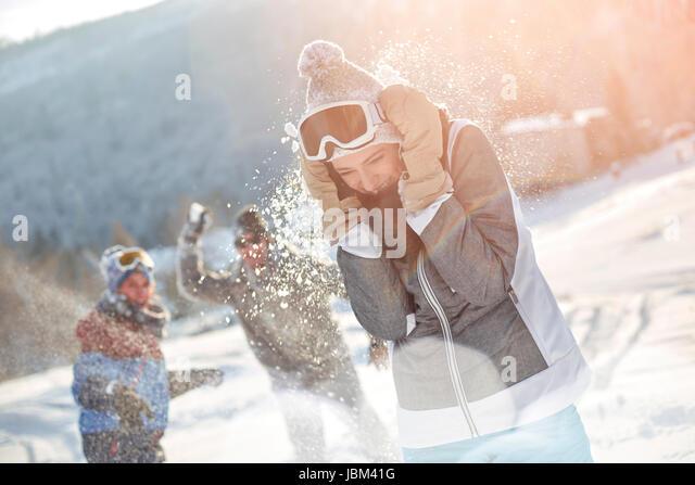 Playful skier friends enjoying snowball fight in snowy field - Stock-Bilder