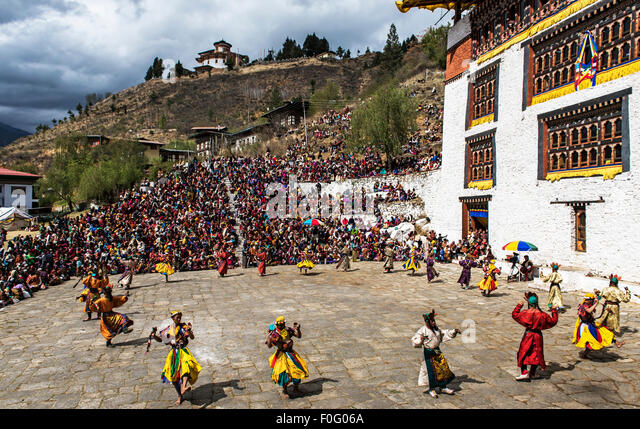 Dancers performing with spectators and temple in the background Paro religious festival Bhutan - Stock-Bilder
