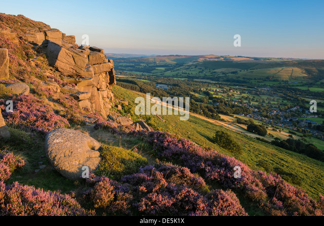 Heather surrounds a millstone on Bamford Edge with the village of Bamford below. Peak District, Derbyshire, England - Stock Image