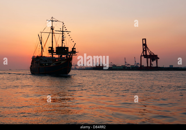 Modern replica of a sailing ship coming to port at sunset in Osaka, Japan. - Stock Image