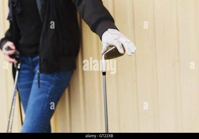 Midsection of woman holding golf clubs while leaning on wall - Stock-Bilder