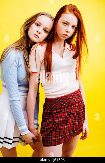 lifestyle people concept: two pretty young school teenage girls having fun happy smiling on yellow background closeup - Stock Image