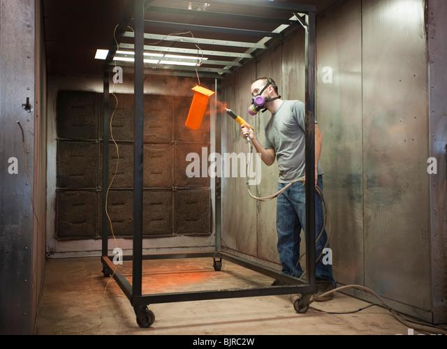 USA, Utah, Orem, man using paint spray gun - Stock Image