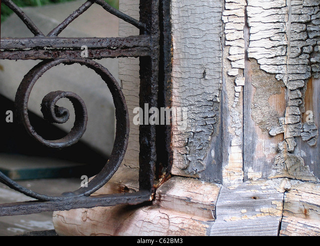 A close up study of a rusty wrought iron railing and cracking paint. - Stock Image