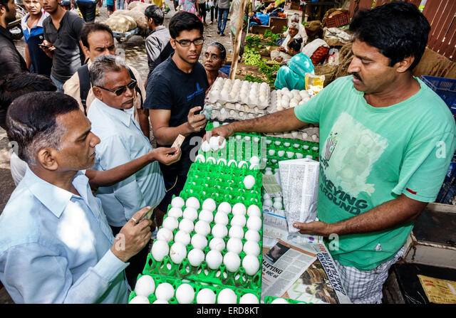 India Asian Mumbai Lower Parel Sunday Market produce vendor shopping selling sale eggs man buying paying - Stock Image