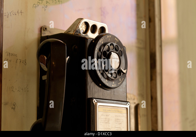 Vintage rotary dial pay phone on wall - Stock Image