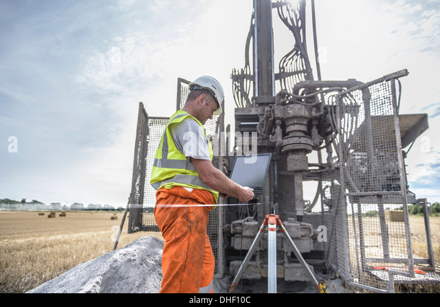 Worker using laptop to survey drilled hole made by drilling rig in field - Stock Image
