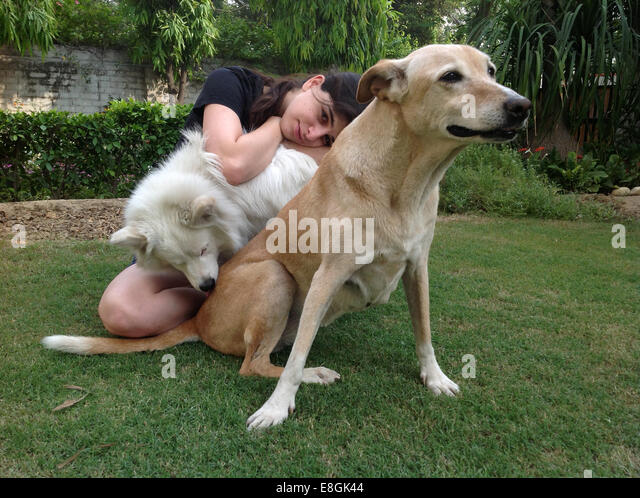 India, New Delhi, Young woman sitting in garden with two dogs - Stock Image