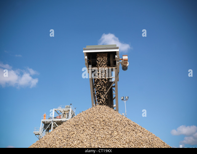 Stones pouring in pile from conveyor - Stock Image