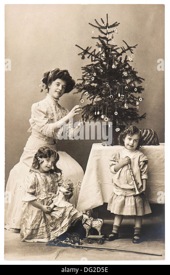 antique family portrait of mother and children with christmas tree wearing vintage clothing - Stock-Bilder