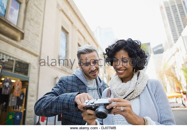 Couple looking at photographs on digital camera - Stock Image