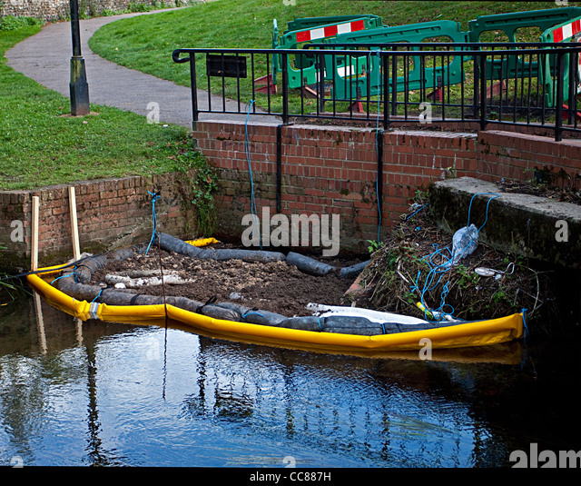 Oil spill spillage pollution in river pollution control environmental Oil booms oil absorbent granules in use - Stock Image