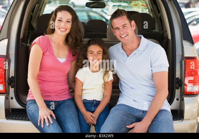 Family sitting in back of van smiling - Stock Image