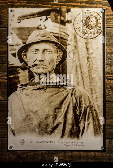 Old archival sepia picture showing close up portrait of fisherman smoking pipe - Stock Image