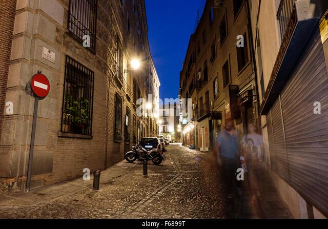 Spain Europe Spanish Hispanic Toledo dusk night nightlife Calle del Horno de los Bizcochos narrow street alley buildings - Stock Image