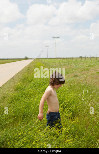 Boy walking in grass in countryside - Stock-Bilder