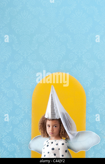 young girl dressed up as a fairy with blue background and yellow arch - Stock Image