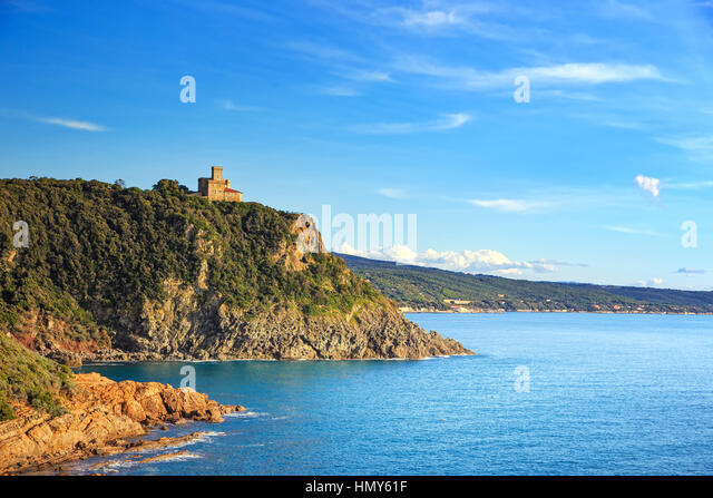 Cliff rock and building on the sea on sunset. Quercianella, Tuscany riviera, Italy, Europe. - Stock Image