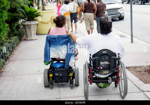 Miami Beach Florida Ocean Drive man woman wheelchairs disabled disability handicap mobility paralysis motorized - Stock Image