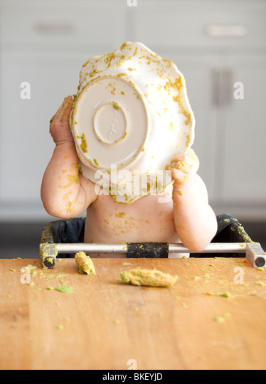 Baby eating bowl of peas - Stock Image