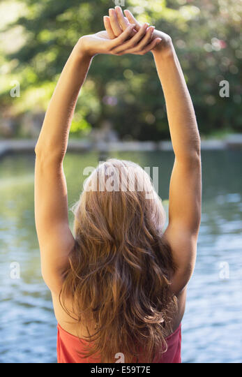 Woman stretching by pool - Stock Image
