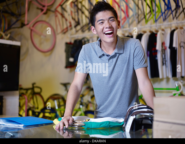 Portrait of young man laughing in bike shop - Stock Image