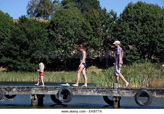 Family strolling on pier, Lake Okareka, New Zealand - Stock Image