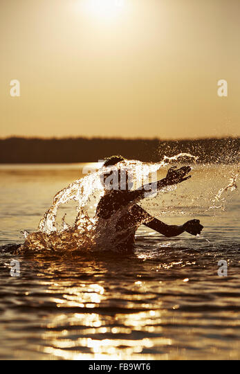 Sweden, Vastra Gotaland, Skagern, Boy (10-11) splashing in lake at sunset - Stock Image