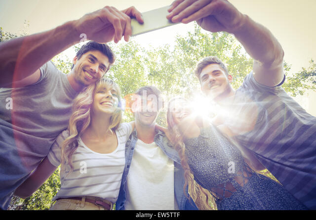 Happy friends in the park taking selfie - Stock Image
