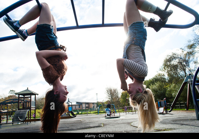 Two 16 17 year old teenage girls, hanging upside down in a playground, UK - Stock-Bilder