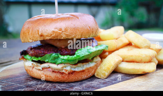 Close up of meat burger with green lettuce, relish in a wheat bun offered on wooden board, accompanied by chunky - Stock Image