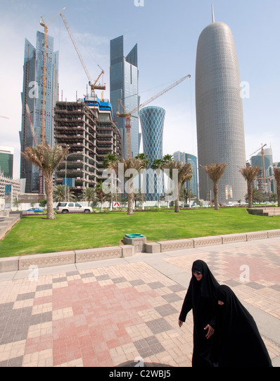 Women walking on The Corniche with modern office towers and skyline in business district in Doha Qatar - Stock Image
