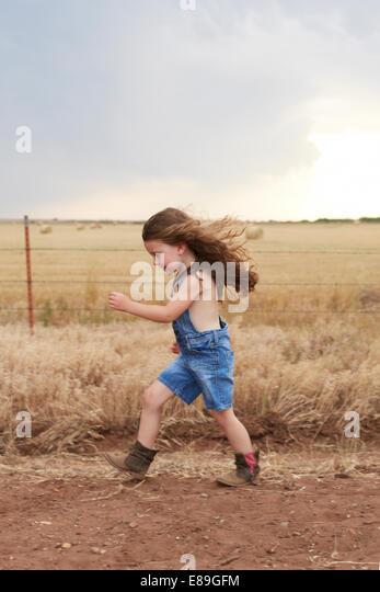 Girl running along country road - Stock-Bilder