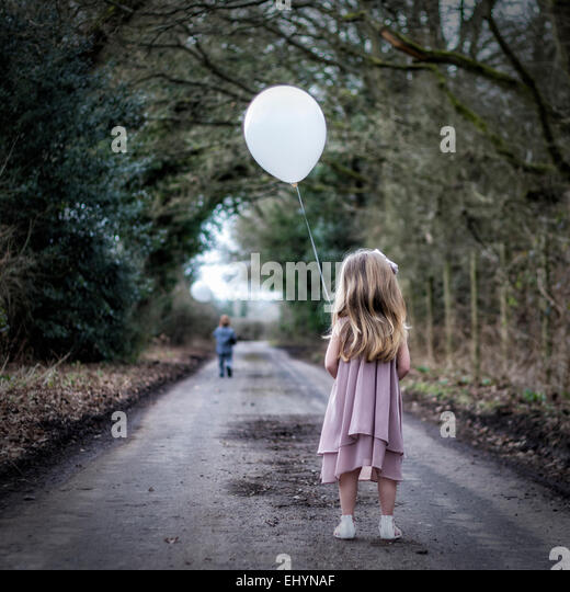 Rear view of girl holding a balloon looking at boy running away from her - Stock-Bilder