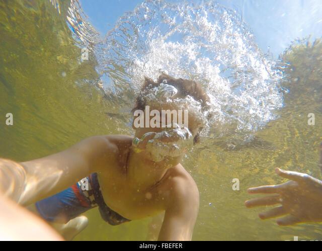 Teenage Boy Swimming Underwater - Stock-Bilder