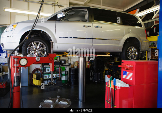 Minivan on a Lift in Shop - Stock Image