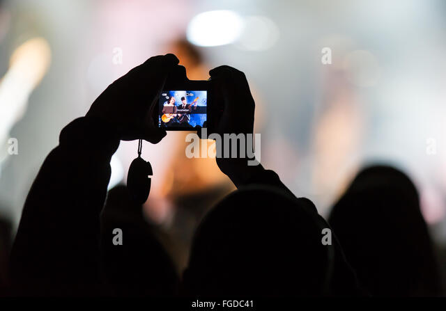 Concertgoers takes a photo with iPhone - Stock-Bilder