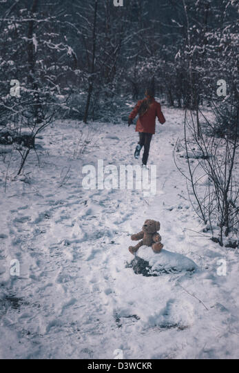 a teddy bear is sitting in the snow, a girl is running away - Stock Image