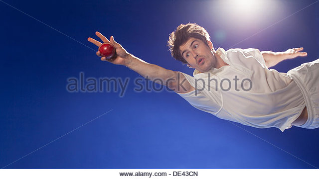 Cricket player catching ball - Stock Image