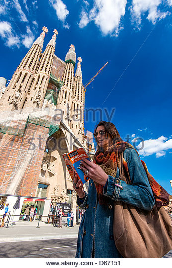 Caucasian female tourist reading a travel guide book with Sagrada Familia behind, Barcelona, Catalonia, Spain - Stock-Bilder