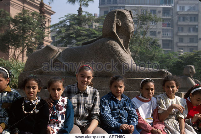 Egypt Cairo Egyptian Museum female Muslim students sphinx statue - Stock Image
