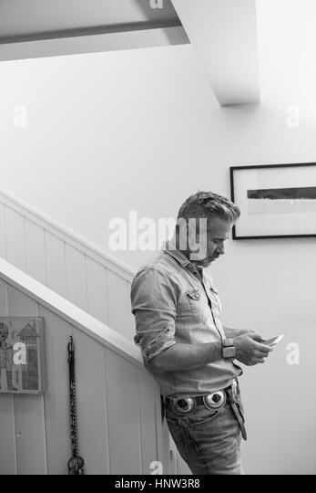 Caucasian man leaning on staircase bannister texting on cell phone - Stock-Bilder