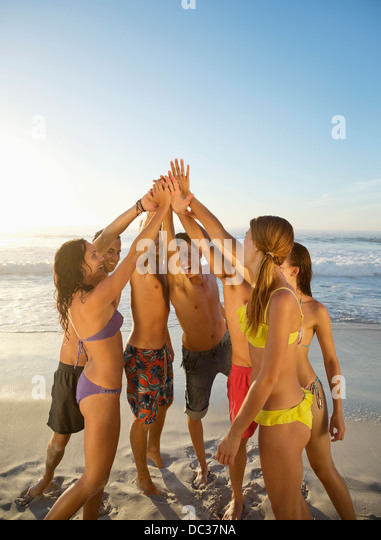 Friends high fiving in circle at beach - Stock Image