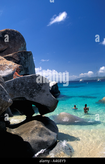 British Virgin Islands The Baths Virgin Gorda tourists in water around large granite boulders - Stock Image
