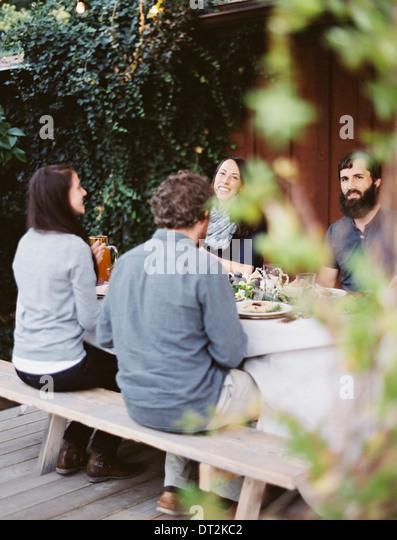 A group of people around a table A celebration meal with table settings and leafy decorations Glasses plates and - Stock Image