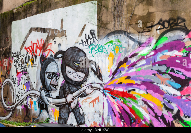 Baby in furry bunny suit with third eye uses hose pipe spraying colours - street art by Alex Face,Pedley Street, - Stock Image