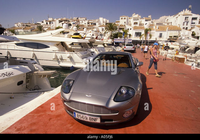 Spain Puerto Banus Marbella Andalucia Porsche in front of luuxery yachts - Stock Image