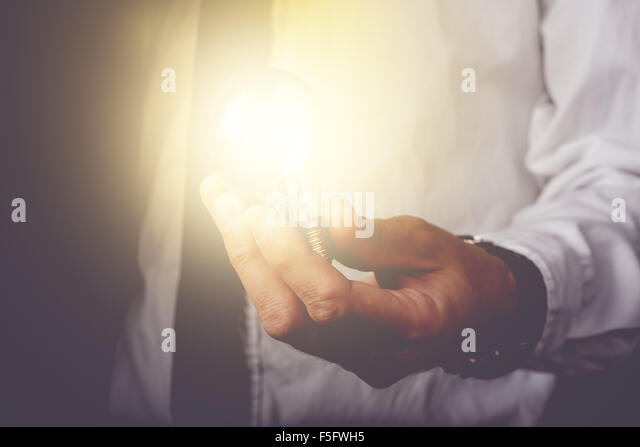 Business idea and vision, businessman holding light bulb, concept of new ideas, innovation, invention and creativity, - Stock Image